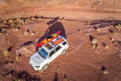 Toyota 4runner SUV met een kajak op dak op een woestijnsleep Royalty-vrije Stock Afbeelding