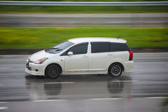 Toyota Wish on wet road in a rainy day. Stock Photo