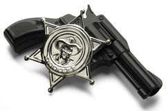 Toys. A toy gun with a sheriff's pin on white Royalty Free Stock Photo