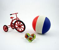 Toys. A cast-iron tricycle, some marbles and a rubber ball stock image