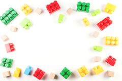 Toys background. Colorful wooden cubes and plastic construction blocks frame on white background Royalty Free Stock Image