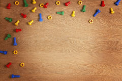 Toys Background Frame Boarder. Colorful nuts and bolts on wooden table. Top view. Flat lay. Copy space for text Royalty Free Stock Images