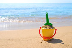 Toys on the beach. Shovel and bucket with sand at the seashore royalty free stock photography
