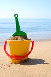 Toys on the beach. Shovel and bucket with sand at the seashore stock photography