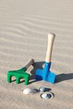 Toys on the beach. Toys lying next to some shells on the beach royalty free stock image