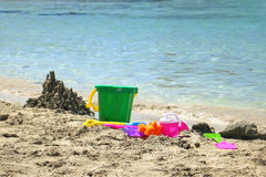 Toys On The Beach. Childrens toys and a little sand castle on the beach stock photography