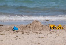 Toys on beach near water. Mountain of sand on a beach near the water with small ripple wave blue toy pail and yellow toy construction trucks stock images