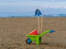 Toys on the beach plastic wheelbarrow, bucket and spade Royalty Free Stock Photography