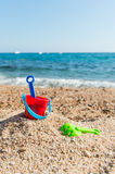 Toys at the beach. Red plastic toy bucket and rake at the beach Royalty Free Stock Images