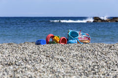Toys on a beach. Some beach toys abandoned in a net on the sea shore royalty free stock image