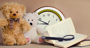 Toys bear cubs sit before round clock Royalty Free Stock Photography