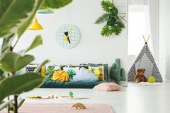 Teepee in bright kid`s room. Toys and clock in bright kid`s room interior with teepee and teddy bear in front of window royalty free stock image