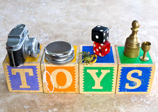 TOYS concept. A selection of children's toys including a toy camera, yo-yo, rubber crab, dice, chess piece and doll house cup on top of a wooden alphabet blocks Stock Photos