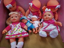 Toys dolls different models and sizes. For sales - a little baby boy among the girls royalty free stock photo
