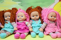 Toys dolls. On shelf besides a colorful wall Royalty Free Stock Photography