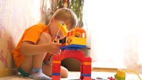 toys för barnspelrum Barn i det modiga rummet som mot efterkrav spelar med objekten för konstruktionsuppsättning från små kuber o arkivfilmer
