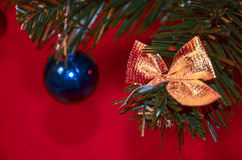 Toys on the faux Christmas tree. Chirstmas ball and bow are hanging on a fir branch Royalty Free Stock Photo