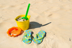 Toys and flip flops at the beach Royalty Free Stock Photography