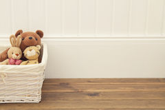 Toys on the floor. Stuffed animal toys in a basket on the floor. A white wainscot Royalty Free Stock Photos