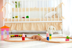 Toys on the floor in sunny baby bedroom with crib on background Royalty Free Stock Photos