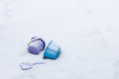 Toys left behind on a snowy ground Royalty Free Stock Images