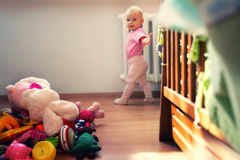 Toys in a mess 2a. Adorable baby girl is showing the mess she made Royalty Free Stock Image