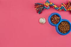 Toys -multi coloured rope, ball and dry food. Accessories for play on pink background top view stock image