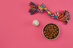 Toys -multi coloured rope, ball and dry food. Accessories for play on pink background top view royalty free stock photos