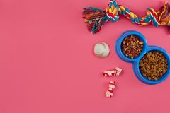 Toys -multi coloured rope, ball, dry food and bone. Accessories for play on pink background top view royalty free stock photo