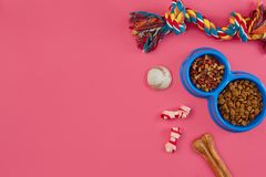 Toys -multi coloured rope, ball, dry food and bone. Accessories for play on pink background top view stock photos