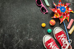 Toys and red sneakers on black chalkboard - childhood. Toys and red sneakers on black chalkboard from above. Childhood - holiday or summer fun concept royalty free stock photo