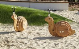 toys of a rocking chair in the form of snails on a modern Playground with a covering from sand stock photos