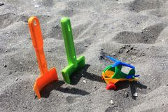 Toys on the sand of the beach in Spain. Toys left on the sand of the beach in Spain. Colourful toys ready for play, to have fun on the beach in the summer day Royalty Free Stock Photos