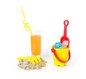 Toys for sand castles and a refreshing drink Royalty Free Stock Images