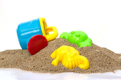 Toys on sand with white background. Royalty Free Stock Image