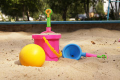 Toys in a sandbox. Baby bucket of sand, shovel, and the ball lie in the sandbox Stock Image