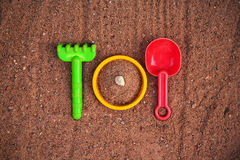 Toys in a Sandbox. Plastic toys (shovel,rake and sieve) arranged as a cutlery and dish in a sandbox Stock Images