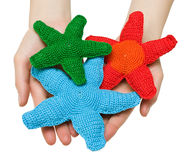Toys - starfishes. Hand made toys - red, green and blue starfishes in female hands. Isolation Stock Photography