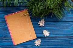 Toys to decorate christmas tree for new year celebration with fur tree branches and notebook on blue wooden background Stock Photo