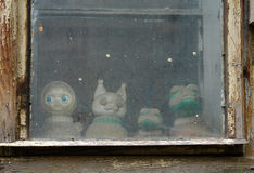 Toys in the window of the old house Royalty Free Stock Photography