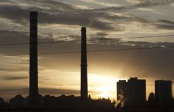 TPP thermal power plant on a sunrise. Refinery with smokestacks. Smoke from factory pollutes the environment. High red and white t. Ower of CHPP. TPP produce royalty free stock photography