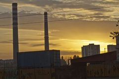 TPP thermal power plant on a sunrise. Refinery with smokestacks. Smoke from factory pollutes the environment. High red and white t. Ower of CHPP. TPP produce royalty free stock photo