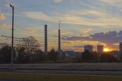 TPP thermal power plant on a sunrise. Refinery with smokestacks. Smoke from factory pollutes the environment. High red and white t. Ower of CHPP. TPP produce royalty free stock image