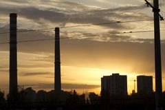 TPP thermal power plant on a sunrise. Refinery with smokestacks. Smoke from factory pollutes the environment. High red and white t. Ower of CHPP. TPP produce royalty free stock photos