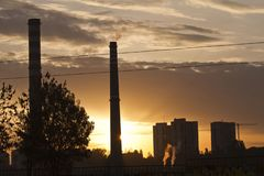TPP thermal power plant on a sunrise. Refinery with smokestacks. Smoke from factory pollutes the environment. High red and white t. Ower of CHPP. TPP produce stock photo