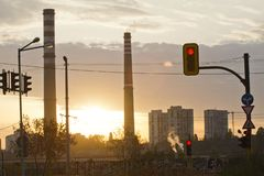 TPP thermal power plant on a sunrise. Refinery with smokestacks. Smoke from factory pollutes the environment. High red and white t. Ower of CHPP. TPP produce stock image