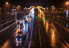 Tráfego da noite na avenida chuvosa da cidade Fotos de Stock Royalty Free