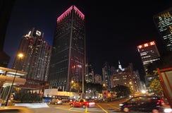 Tráfego da rua da noite de Hong Kong e raspadores do céu Foto de Stock Royalty Free