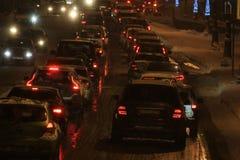Tráfego de carro em uma noite do inverno durante uma queda de neve imagens de stock