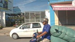 Tráfego do 'trotinette' ao longo da rua após lojas pequenas das casas filme